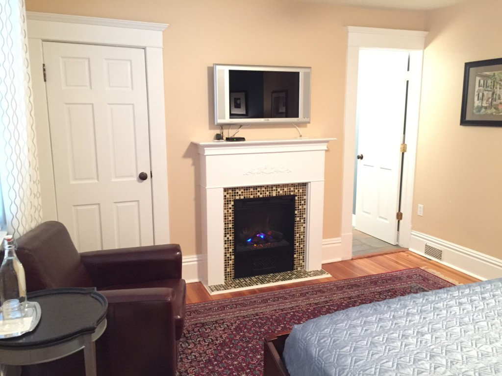 Glass-tiled hearth and surround, comfortable leather club chair and flat-panel LCD TV with expanded cable.